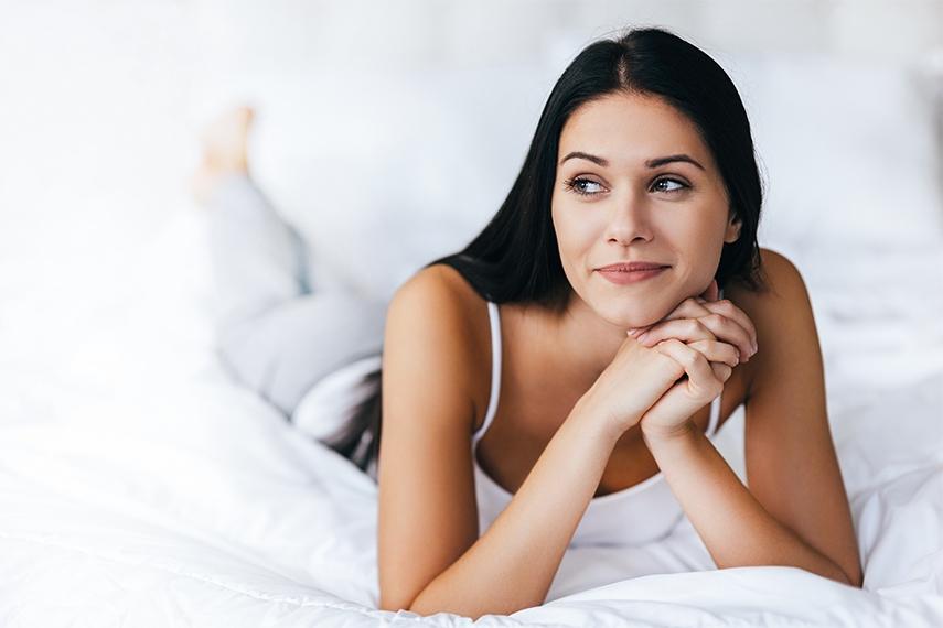 Frau mit makelloser Haut dank Unike Anti Aging Kapseln liegt auf ihrem Bett und sieht verträumt in die Ferne.