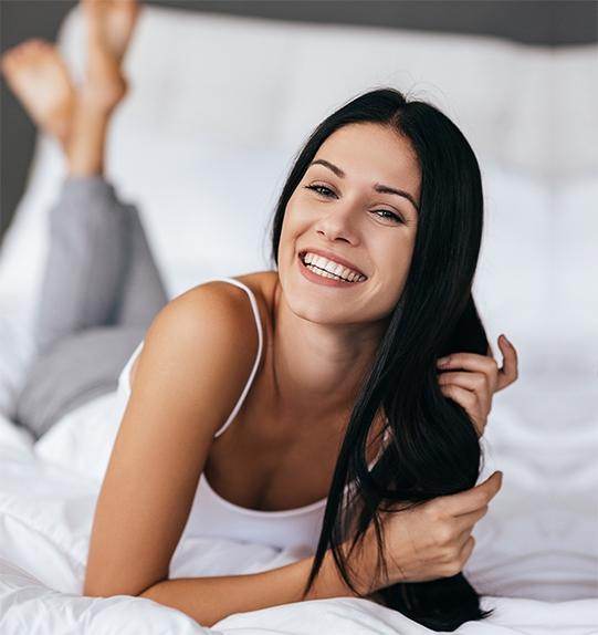 Frau mit gesunden langen Haaren und makelloser Haut dank Unike Anti Aging Kapseln lacht in die Kamera.