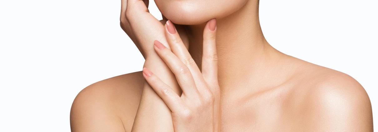 Faltenfreies Kinn, Hals und Dekolletee einer Frau, die sich mit den Händen ans Gesicht fässt. Schöne Haut & Nägel dank den Unike Kapseln